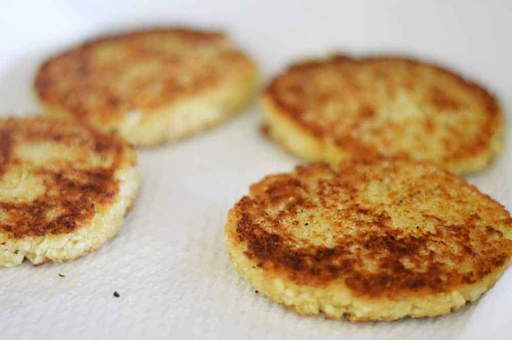 Draining cauliflower fritters on paper towels to remove excess oil