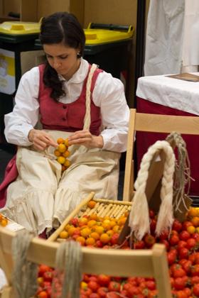 Puglian girl tying bunches of Torre Canne Regina tomatoes
