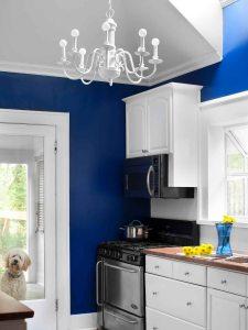 blue kitchen with white backsplash and chandelier