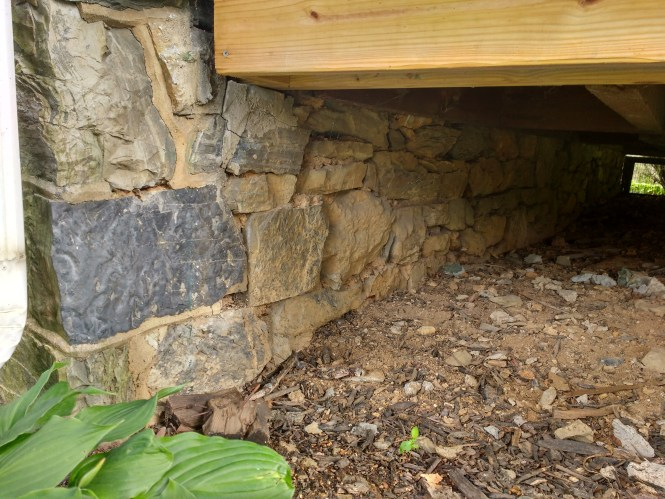 Stone foundation in need of repair with hydraulic lime