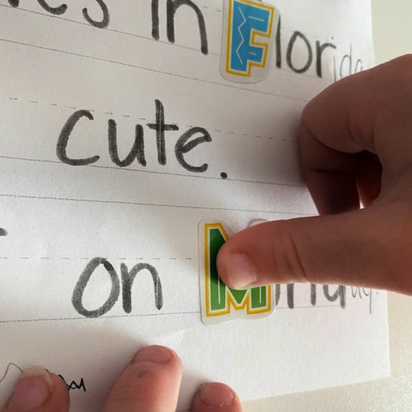 child placing a letter stick on a page of words