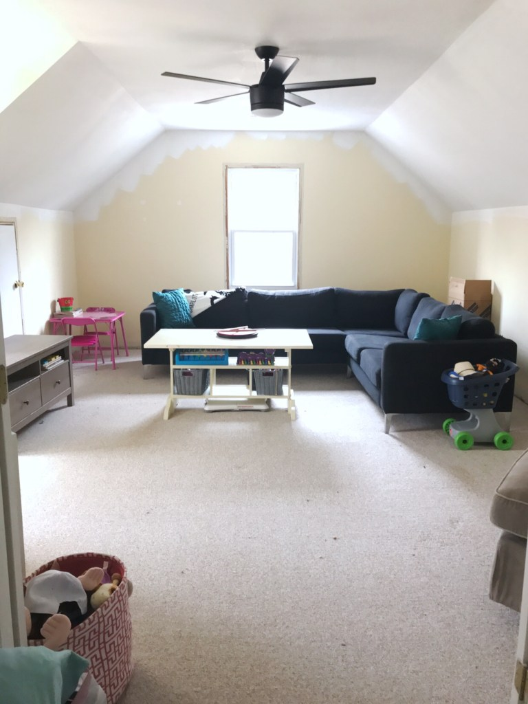 playroom with yellow wall and sectional couch in front of the window