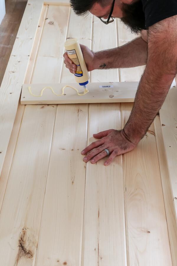 man with beard adding wood glue to center piece of DIY barn door