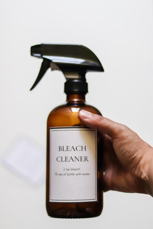 hand holding DIY bleach cleaner