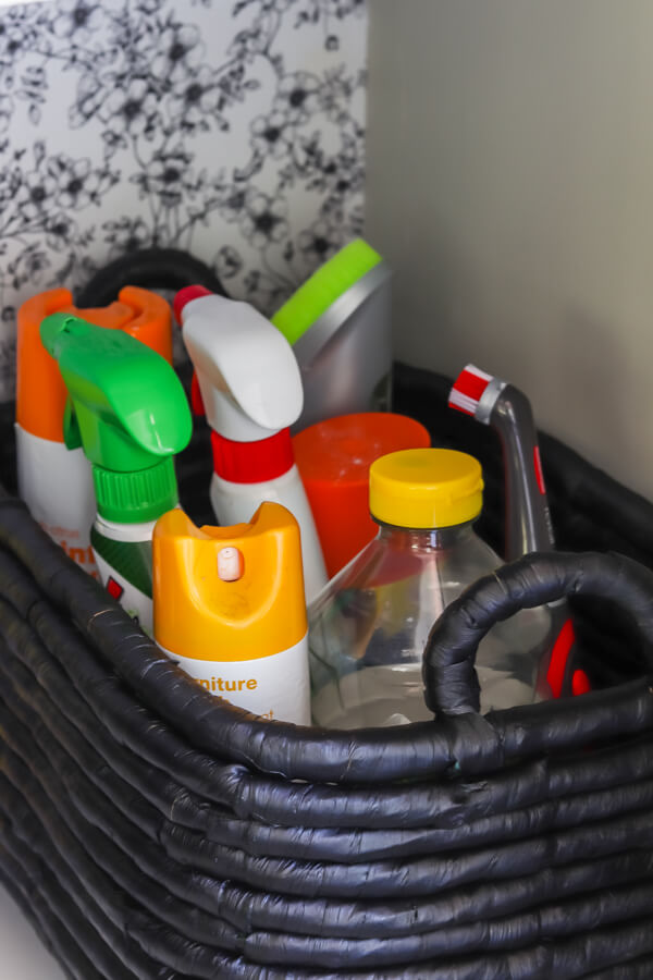 black storage basket with cleaning supplies