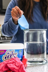 woman pouring OxyClean into glass container with water