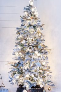 flocked christmas tree with lights on decorated with gold and white ornaments