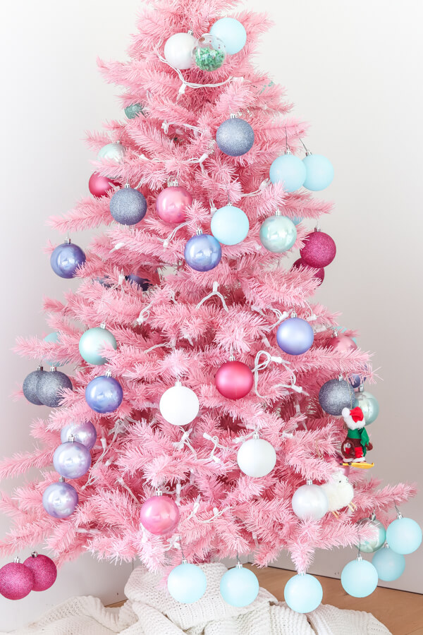closeup of colorful ornaments on pink Christmas tree