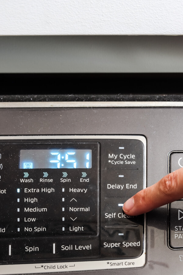 woman's hand pushing self clean cycle on front of front load washing machine