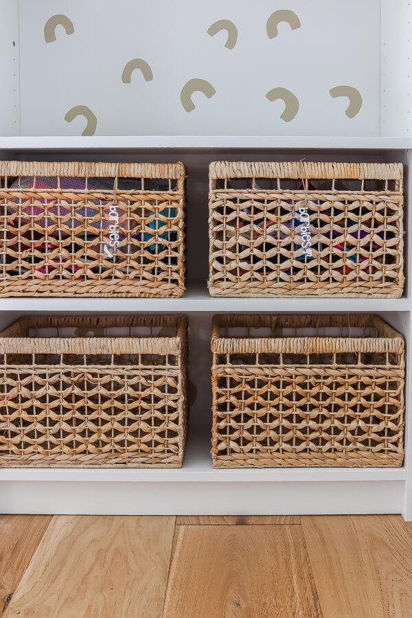 rattan storage baskets on white Ikea Billy bookcases
