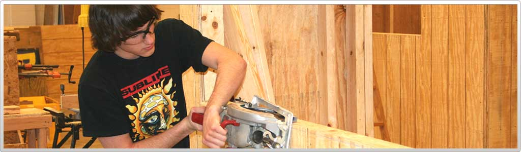 student using buzz saw to cut wood