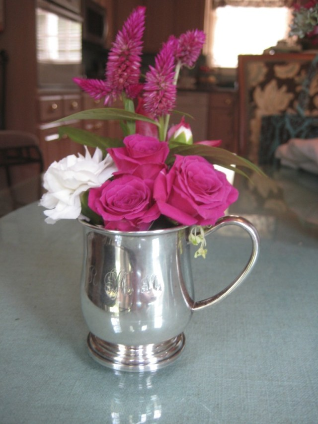 Use silver baby cups to create floral arrangements for a baby shower