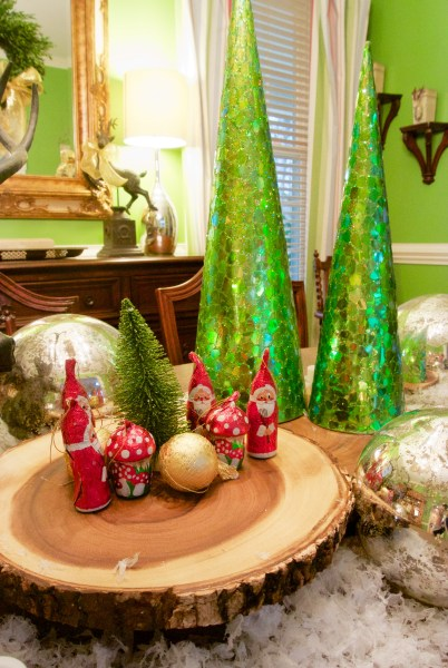 Christmas Decorating Is Easy With Cone Shaped Trees- woodland Christmas tablescape with cone trees, bottle brush trees, wood slices and foil wrapped chocolates from Switzerland
