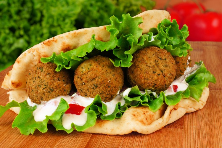 Falafel With Vegetables And  Tzatziki Sauce In Pita Bread Close-up On Wooden Table