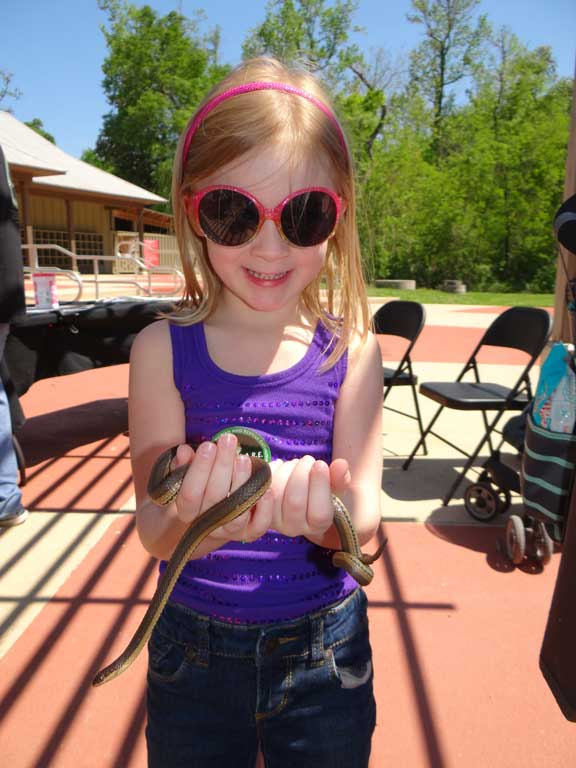 Happy young girl holding a harmless snake.