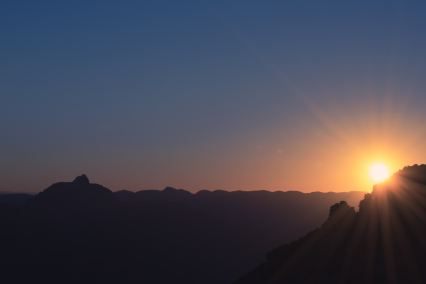 A sun rising behind the mountains