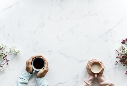 Two people holding cups as illustration to the blogpost of communication by Liz BlackX  Image by rawpixel from Pixabay