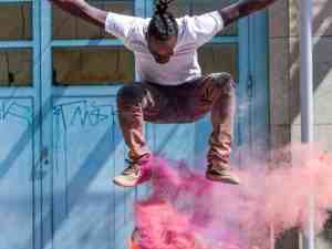 Stunning image of a skateboarder performing an ollie with red smoke