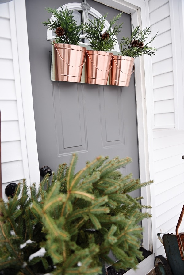 DIY hanging buckets - door decor - A great alternative to a wreath on the door & you can change out the greenery with the season. Also, all items used from the dollar section!