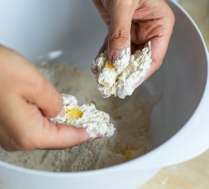 Rubbing butter into flour with fingertips to make scone mixture