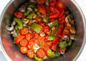 Cooked tomatoes, mushrooms and peppers in a pan to make vegetable sauce for homemade lasagne