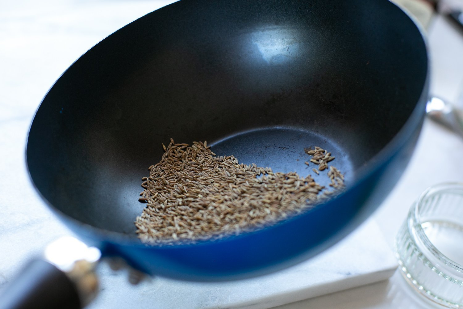 toasted cumin seeds in a pan for Curried aubergine and potato