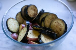 Spiced potato and aubergine slices in a bowl for curried aubergine and potato