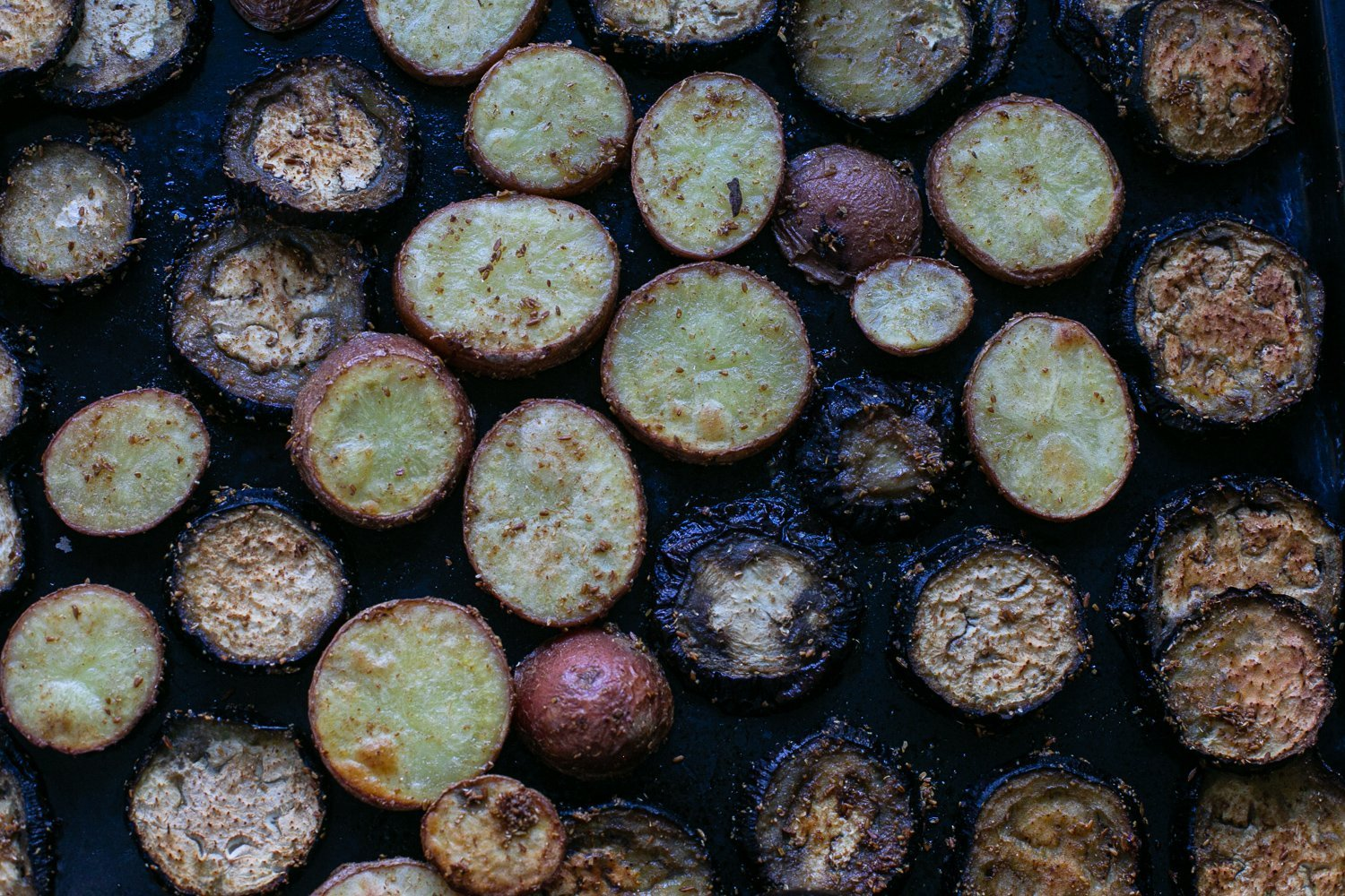 roasted curried aubergine and potato slices on a baking sheet