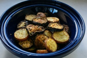 Curried aubergine and potato slices in a dish
