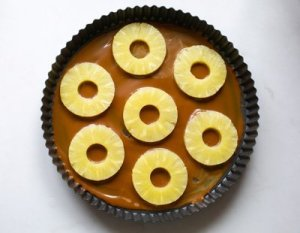 caramel and pineapple pieces in the base of a flan dish ready for the pineapple sponge cake