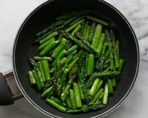 sautéed asparagus in a pan for asparagus pea and leek risotto