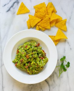 Easy homemade guacamole served in a bowl with tortilla chips