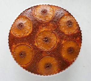 Caramel pineapple summer sponge cooling on a cake stand