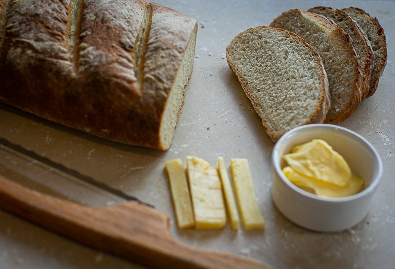 Freshly baked sliced bloomer bread served with butter and cheese