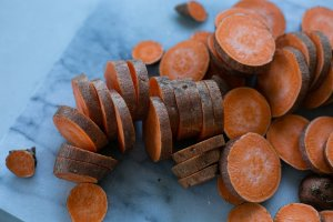 Thinly sliced sweet potato on a chopping board ready to roast