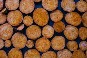 Paprika coated sweet potato slices on a baking tray ready to roast