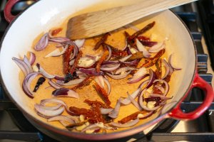 onion, sun dried tomatoes and garlic cooking in a pan to make special rice