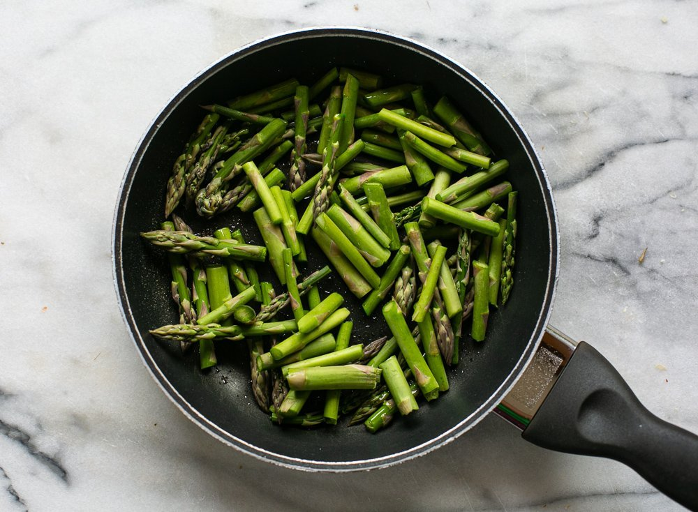 Chopped asparagus cooking in a pan for a risotto