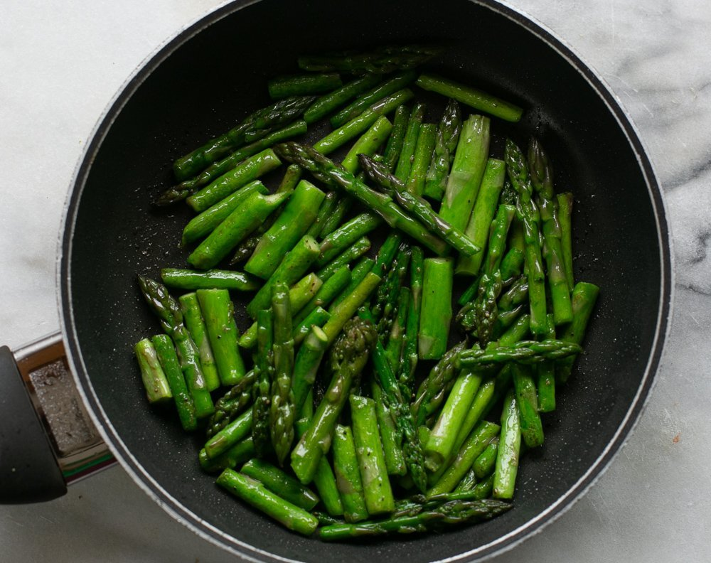 Sautéed asparagus in a pan for a risotto recipe