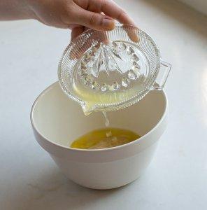 lemon juice being added to a bowl of baba ganoush