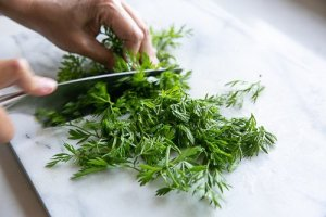carrot leaves being chopped to make Carrot and nectarine salad