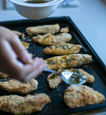 cooked chicken being coated with garlic butter sauce