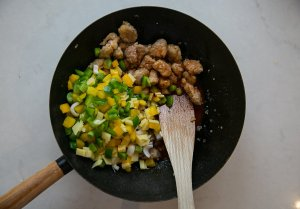 Pork, vegetables and sauce cooking in a wok