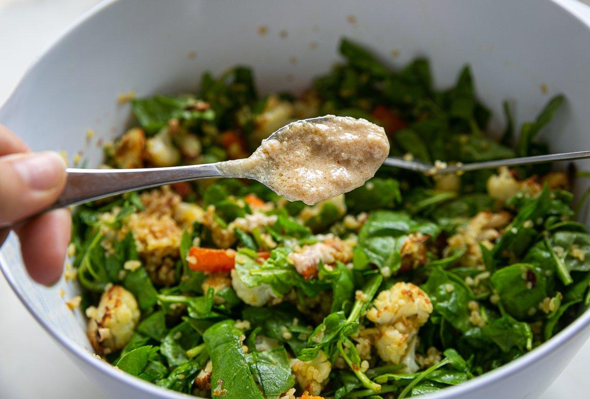 Tahini dressing being added to tahini roasted cauliflower salad