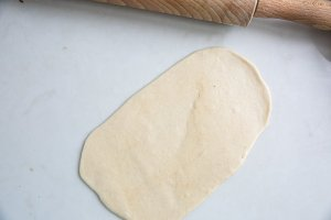 A piece of rolled naan dough on an oiled surface