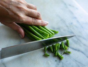 green beans being trimmed with a knife