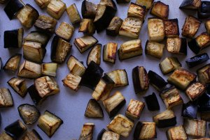 roasted aubergine chunks on a baking tray