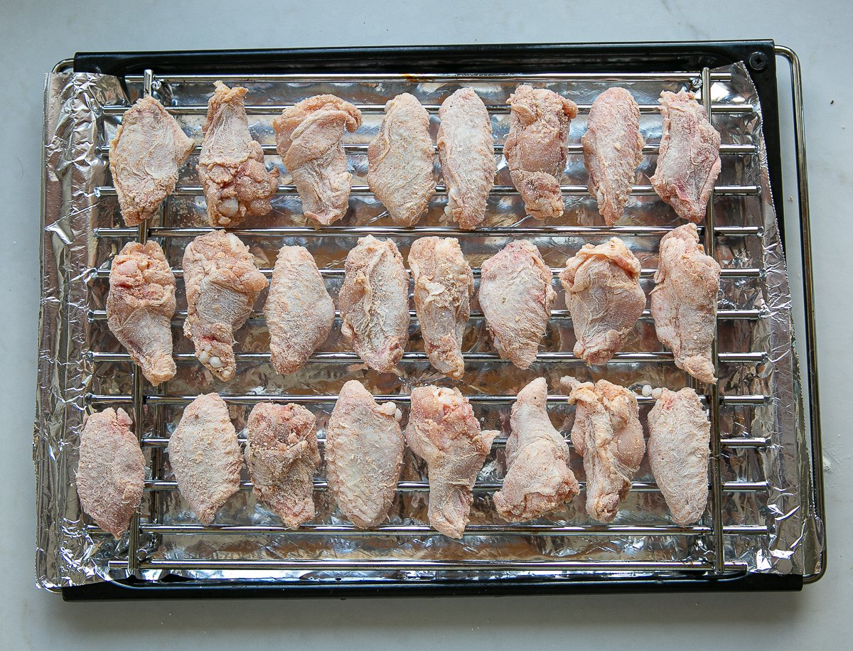 chicken wings ready to cook on a foil lined baking tray