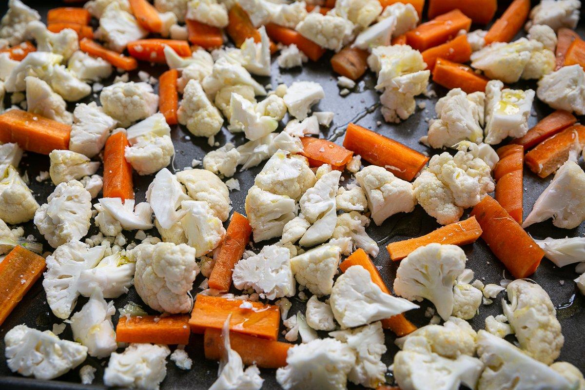 Cauliflower and carrots on a baking tray ready to roast