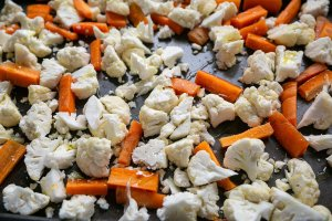 Cauliflower and carrots on a baking tray ready to roast